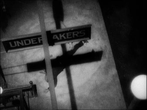 "Whether by neon sign or shadows, the film features an ""X"" motif throughout. This is one caused by shadows of an ""Undertakers"" sign"