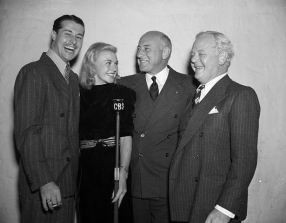 Cecil B. DeMille Posing With Actors at CBS Microphone