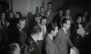 Robert Taylor is escorted into the hearings