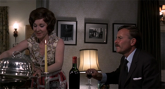 Mrs. Oxford serves a meal while the Inspector talks murder