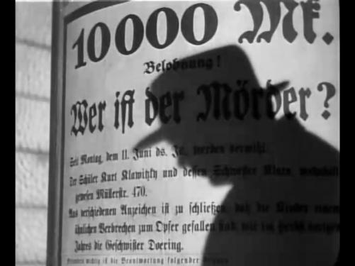 Hans Beckert's profile in shadow falls upon the sign offering a reward for the killer of children.