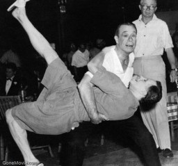 Joe E. Brown (Osgood Fielding III) teaches Jack Lemmon (Daphne) how to tango. Wilder observes.