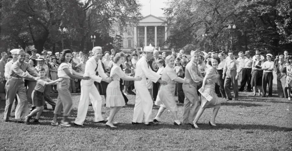 Sailors and Washington, DC residents form a conga line in Lafayette Park while waiting for President Truman to announce Japan's surrender.