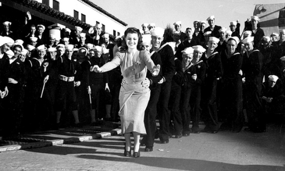 Rita Hayworth leads a conga line of sailors during WWII