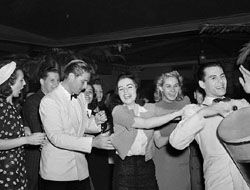 Desi Arnaz with his drum leading a conga line in 1939 in a New York City night spot with Errol Flynn dancing along