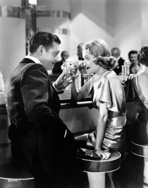 ca. 1935 --- Clark Gable and Constance Bennett toast in a scene from the 1935 film, . --- Image by © John Springer Collection/CORBIS