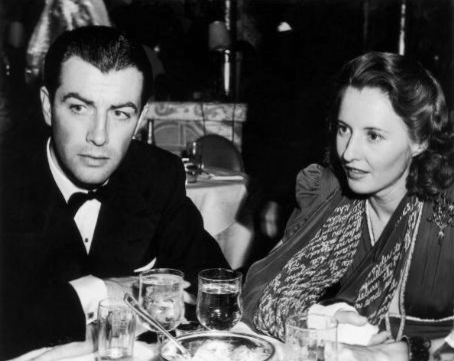 ca. 1938. Married American actors Robert Taylor (1911-1969) and Barbara Stanwyck (1907-1990) sit at a table in a restaurant, wearing formal attire. Stanwyck wears a cast on her forearm and uses a printed scarf as a sling.
