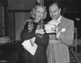 Virginia Bruce reading her fan mail with film director Edwin Marin