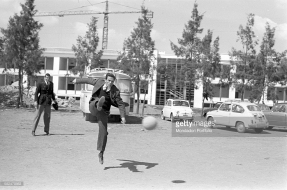 Pier Paolo Pasolini (1922 - 1975) kicking a football during a break in the filming of his drama, 'Accattone'