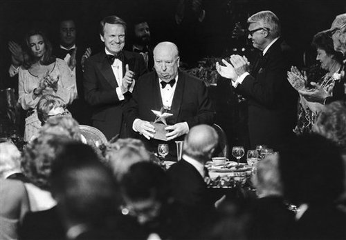 American Film Institute Award and producer and director Alfred Hitchcock, center, stands to receive the applause of producer George Stevens Jr., left, and actor Cary Grant at the Institute's testimonial dinner in Beverly Hills, California, United States, on Wednesday, March 8, 1979. Hitchcock received the Seventh Annual Life Achievement Award in a 90-minute tribute to the veteran film maker. (AP Photo/Huynh Thanh My)