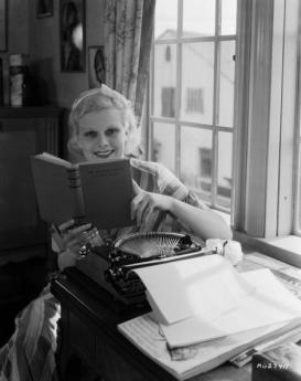 Harlow reading Red-Headed Woman novel at her typewriter