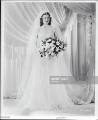 Lucille Ball modeling a wedding gown