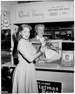 Christmas seal booth, 9 December 1953. Rhonda Fleming;Mrs Homer D Root. (Handout).Los Angeles; California; USAChristmas;Postage-stamps. (Photo by Los Angeles Examiner/USC Libraries/Corbis via Getty Images)