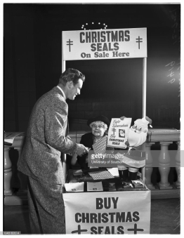 Christmas seal booth opened...subway terminal building, 7 December 1951.;Richard Webb, Actor;Mrs Helen Miller, in charge of booth.;Supplementary material reads: 'Los Angeles County Tuberculosis & Health Assn. Bob Scholl. DUnkirk 8-3401. 1951- 12-07. Photo Identification: #209: Warner Bros. 'Distant Drums' star Richard Webb and Mrs Helen Miller, in charge of booth. At the Christmas Seal booth opened today at the Subway Terminal Building in downtown Los Angeles. Other downtown booths are located at the Spring Arcade Building and at the. E Building at 6th and Main. A fourth booth opens Monday at the Biltmore Hotel'.. (Photo by Los Angeles Examiner/USC Libraries/Corbis via Getty Images)